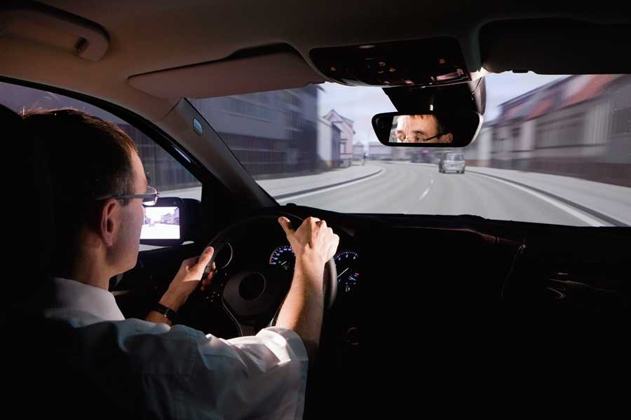 A man sitting at the wheel of a realistic driving simulator